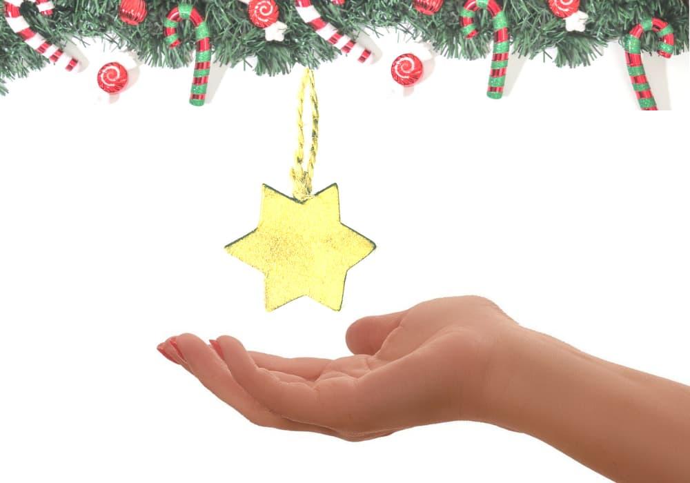 hand holding star under Christmas tree